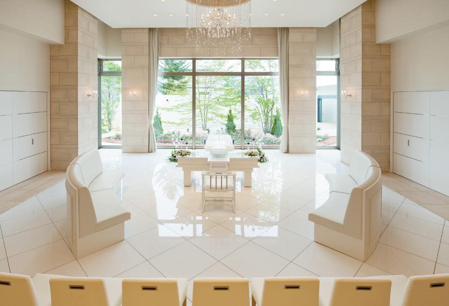 ウィズハウス手稲の葬儀式場「刻のガーデン」。白を基調とした明るいホールでシャンデリアが美しい