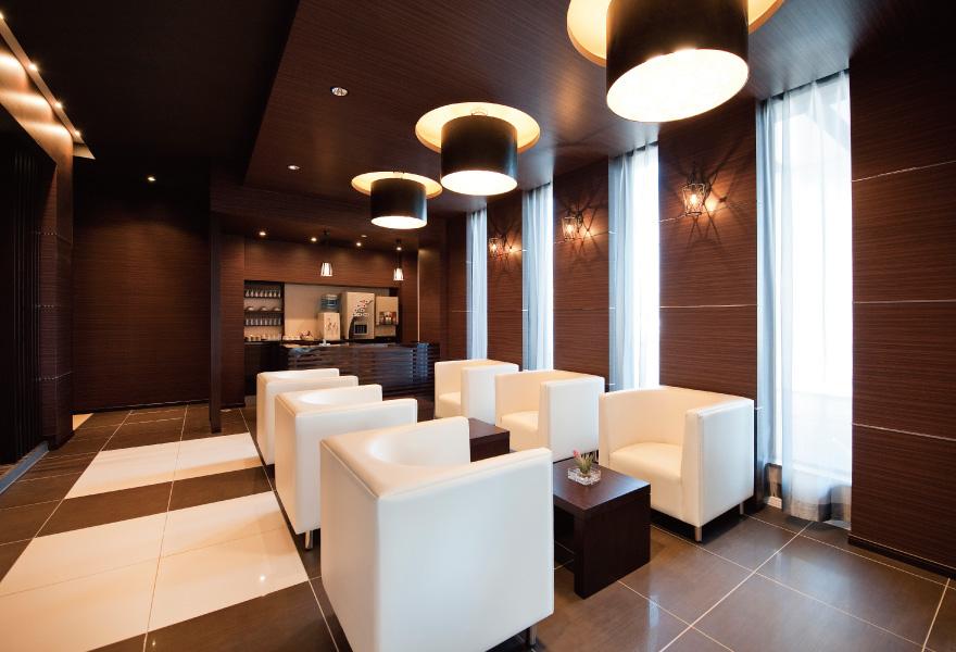 ウィズハウス手稲のラウンジ・メインダイニング。深い茶色を基調とした落ち着いたシックな雰囲気。白いソファの座り心地か良い
