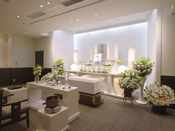 シティ・ホール呉中央の葬儀式場「ファミリエ」。40名程度が定員で小~中規模の家族葬に最適。白き祭壇が美しいしつらえ