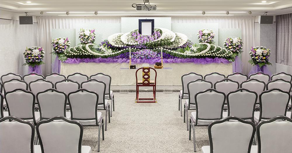 戸田葬祭場の葬儀式場「光の間」の写真。90席の椅子席を用意できる他、プロジェクターも用意されている